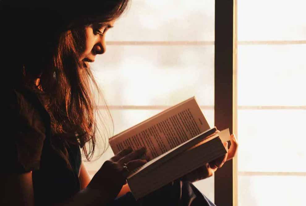 A girl reading a book near the windows.